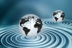 Globes on water ripples Royalty Free Stock Photos