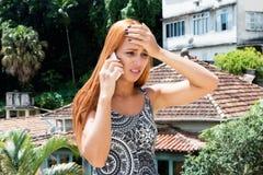 Globetrotter γυναίκα με την κόκκινη τρίχα που λαμβάνει τις κακές ειδήσεις στο τηλέφωνο Στοκ Φωτογραφίες
