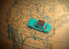 Toy car with luggage on a globe. Toy car with luggage on a vintage globe map of the United States with a shallow depth of field Stock Photos