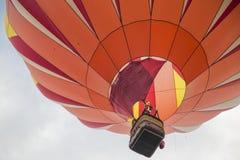 Globo anaranjado del aire caliente en el cielo Imágenes de archivo libres de regalías