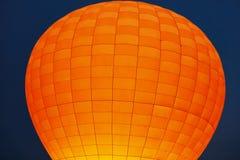 Globo anaranjado del aire caliente en primer azul marino del cielo imagen de archivo