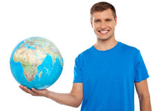 Globo atrativo da terra arrendada do homem novo em sua mão Fotografia de Stock Royalty Free