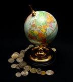 Globo azul del mundo con las monedas Imágenes de archivo libres de regalías