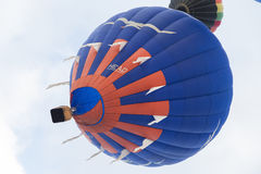 Globo azul y anaranjado del aire caliente en el cielo Fotos de archivo libres de regalías