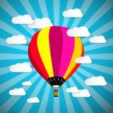 Globo colorido del aire caliente en el cielo azul con las nubes de papel Imágenes de archivo libres de regalías