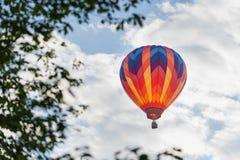 Globo colorido del aire caliente enmarcado por las hojas foto de archivo libre de regalías