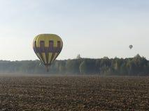 Globo colorido del aire caliente que vuela sobre paisaje de la roca en cielo azul fotografía de archivo