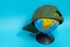 Globo com um bon? de beisebol verde nele em um fundo azul imagens de stock royalty free