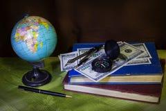 Globo con el dinero, el compás y el libro Imagen de archivo