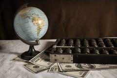 Globo con l'abaco e le banconote in dollari Fotografie Stock