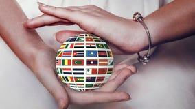 Globo con las banderas de diversos estados en manos femeninas almacen de video