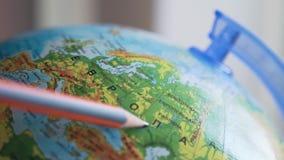 Globo con los nombres rusos de las ciudades y de los países, lápiz principal en el mapa almacen de metraje de vídeo