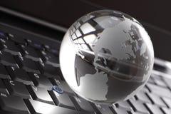 Globo cristalino en el teclado de la computadora portátil Foto de archivo