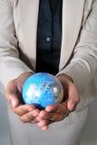Globo da terra arrendada da mulher de negócio em suas mãos Foto de Stock Royalty Free