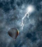 Globo de aire caliente entre las nubes con el relámpago Foto de archivo libre de regalías