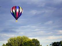Globo de aire caliente pilotado colorido vibrante del helio en vuelo Fotos de archivo