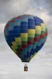 Globo de aire caliente que flota entre las nubes Imagen de archivo libre de regalías