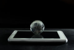 Globo de cristal en la tableta del ordenador fotos de archivo