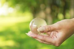 Globo de cristal en manos Imagen de archivo