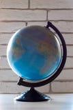 Globo de giro Globo de la tierra en un fondo de la pared de ladrillo Imagen de archivo libre de regalías