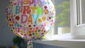 Globo de la celebración del partido del feliz cumpleaños en la luz del sol reflectora giratoria de la ventana metrajes