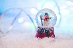 Globo de la nieve con el fondo blured muñeco de nieve feliz Fotografía de archivo libre de regalías