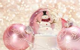 Globo de la nieve con los ornamentos rosados Fotos de archivo libres de regalías