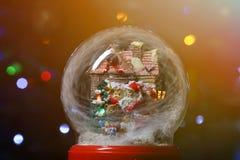 Globo de la nieve con Santa Claus cerca de la casa con la linterna de la calle Imagen de archivo libre de regalías