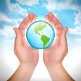 Globo de la tierra de la explotación agrícola de la mano en cielo Imagenes de archivo