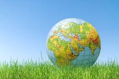 Globo de la tierra del planeta sobre hierba Fotografía de archivo libre de regalías