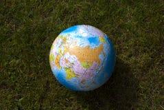 Globo de la tierra en la hierba Imágenes de archivo libres de regalías