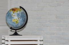 Globo de la tierra en un fondo de la pared de ladrillo imagen de archivo libre de regalías