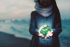 Globo de la tierra que brilla intensamente en las manos de la mujer en la playa en la noche foto de archivo