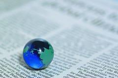 Globo de vidro sobre o jornal Fotografia de Stock Royalty Free