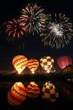 Globo del aire caliente del resplandor de la noche con el fuego artificial hermoso Imágenes de archivo libres de regalías