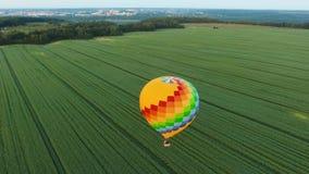 Globo del aire caliente en el cielo sobre un campo