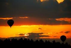 Globo del aire caliente en puesta del sol Foto de archivo