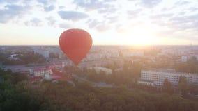 Globo del aire caliente que flota sobre la ciudad en el amanecer, sol que sube en el horizonte, aspiraciones almacen de video