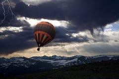 Globo del aire caliente que se escapa sobre picos de montaña Imágenes de archivo libres de regalías