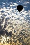 Globo del aire caliente que sube en la salida del sol Imagenes de archivo