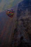 Globo del aire caliente que vuela sobre campos del invierno Imagen de archivo