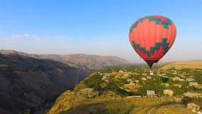 Globo del aire caliente que vuela sobre el pueblo y las montañas hermosos de Halidzor del armenio almacen de metraje de vídeo