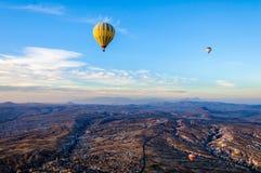 Globo del aire caliente que vuela sobre los valles en Cappadocia Turquía Fotos de archivo