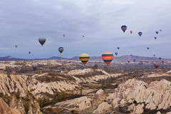 Globo del aire caliente que vuela sobre paisaje de la roca en Cappadocia Turquía Imágenes de archivo libres de regalías