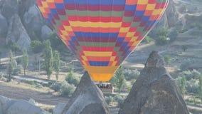 Globo del aire caliente rayado con una cesta de turistas que vuelan arriba en el cielo almacen de metraje de vídeo