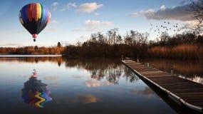 Globo del aire caliente sobre el lago de la puesta del sol con el embarcadero Imagen de archivo libre de regalías