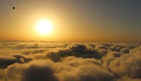 Globo del aire caliente sobre las nubes en salida del sol Foto de archivo