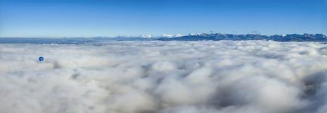 Globo del aire caliente sobre las nubes que ven las montañas de las montañas Fotos de archivo