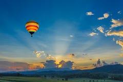 Globo del aire caliente sobre los campos en la puesta del sol Fotografía de archivo