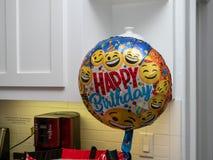 Globo del feliz cumpleaños con las caras de la sonrisa que flotan en una casa lista para el partido foto de archivo libre de regalías